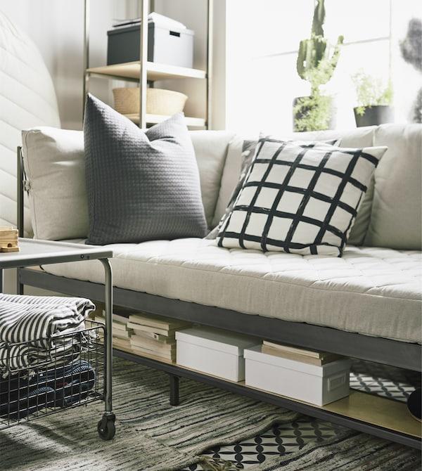 Le mobilier gain de place est une solution parfaite pour les petits appartements. L'astucieux canapé EKEBOL IKEA, en beige et acier, intègre des tablettes de rangement dans le bas et derrière.