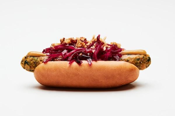 Le nouveau hot-dog végétarien de IKEA est garni de chou rouge mariné, d'oignons frits croustillants et de moutarde brune.