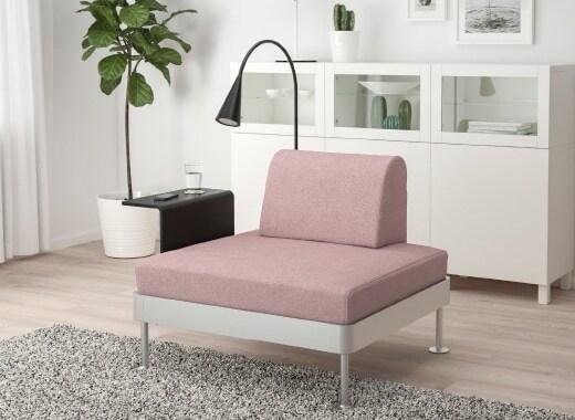 Le nuove fodere DELAKTIG sono più durevoli e resistenti: qui in rosa su una poltrona con tavolino nero e lampada a LED – IKEA