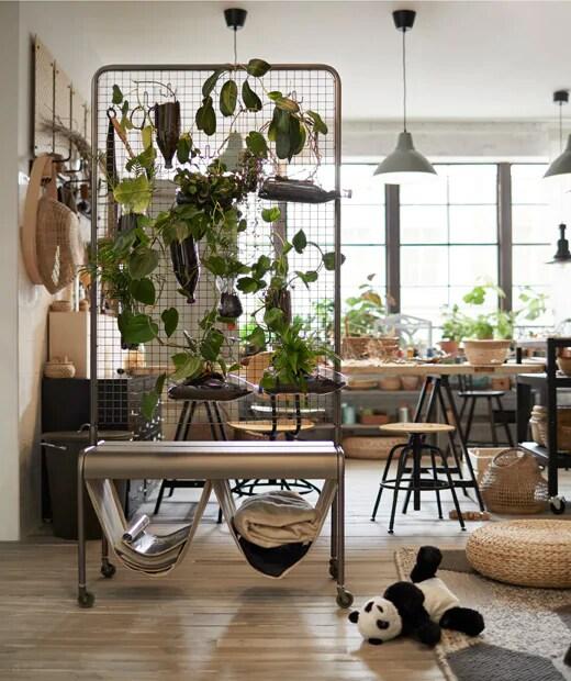 Le paravent VEBERÖD est couvert de plantes et il sépare l'espace bureau du coin jeu dans une pièce lumineuse où l'acier noir et le bois clair s'harmonisent joliment.