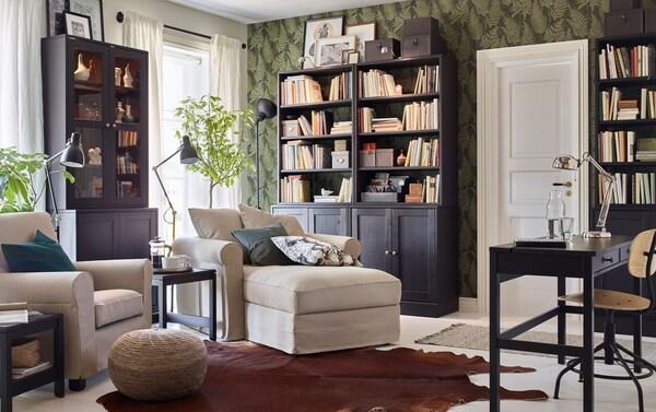 Le séjour est aménagé de deux fauteuils IKEA GRÖNLID beige clair et de vitrines et d'étagères de rangement ouvertes HAVSTA brun foncé, pour un style moderne.