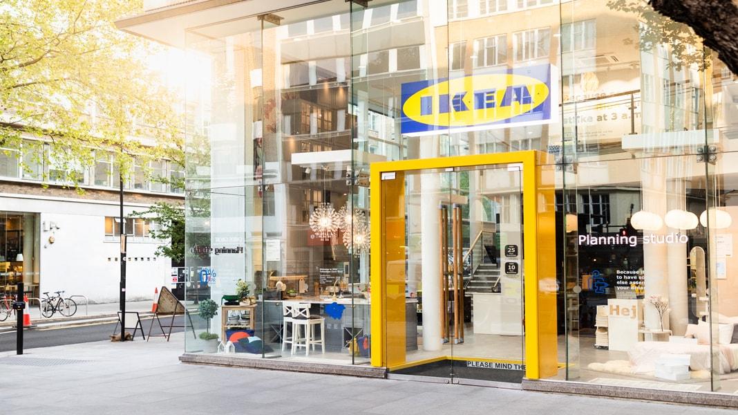 Le soleil rayonne à travers la devanture en verre d'un magasin IKEA situé dans un centre-ville. Une structure jaune vif encadre l'entrée.