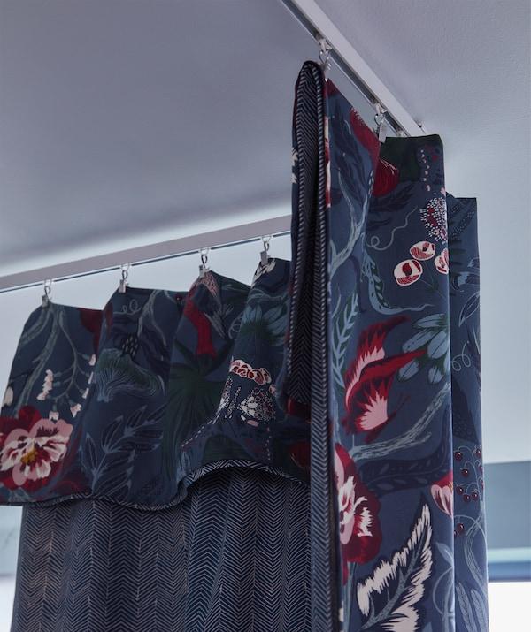 Le tissu IKEA FILODENDRON est bleu foncé avec un motif floral dans les tons bleu clair, blanc, rouge, rose et mauve.