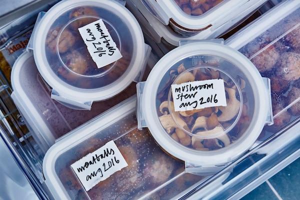 Lebensmittel in Vorratsbehälter mit Etiketten in einem Kühlschrank