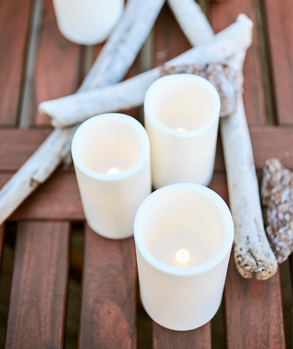 LED block candles on a wooden table with driftwood.