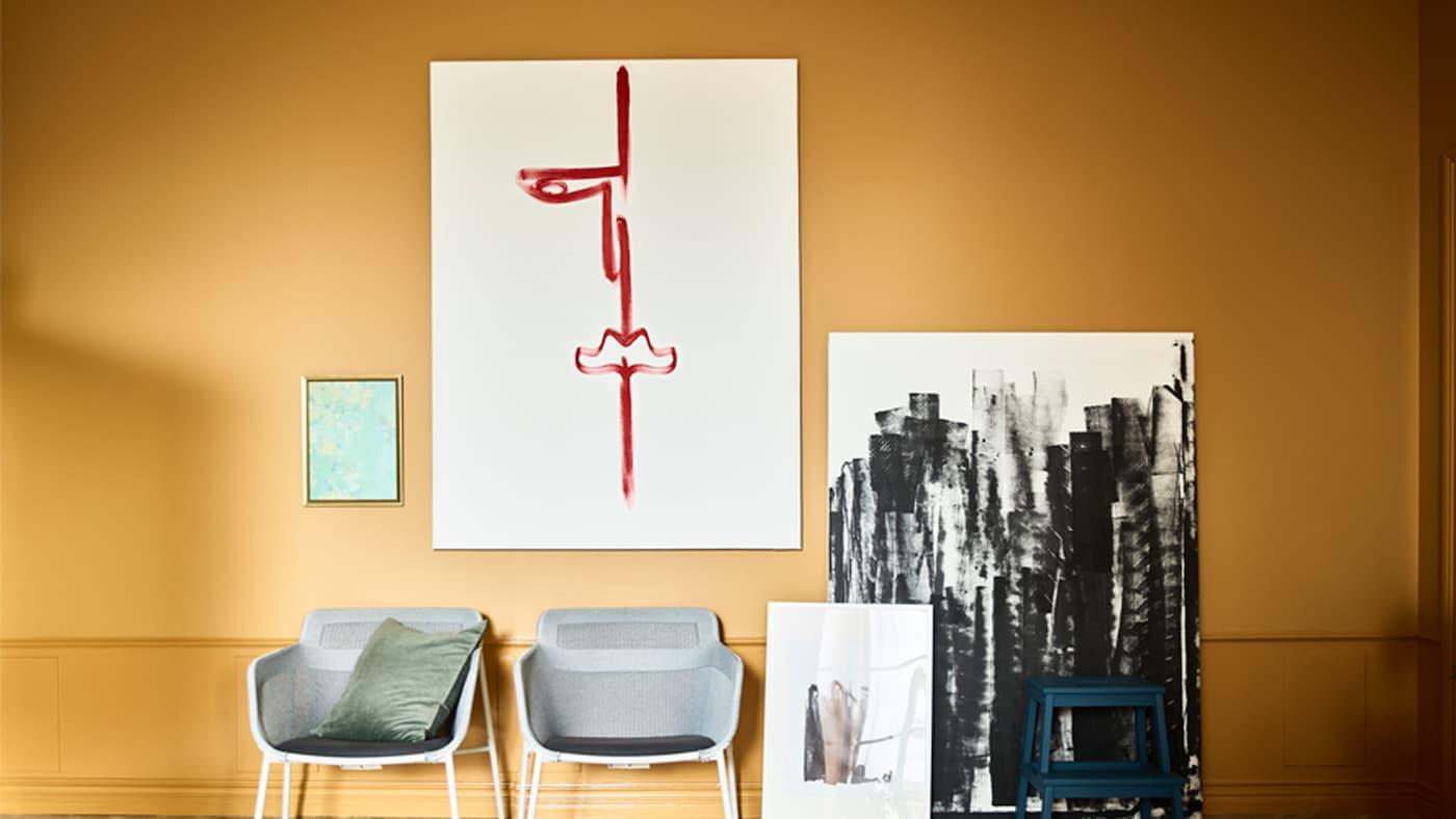 Leinwände hängen und lehnen an einer ockerfarbenen Wand. Sie sind mit schwarzen und roten Pinselstrichen bemalt. Davor stehen zwei Stühle.