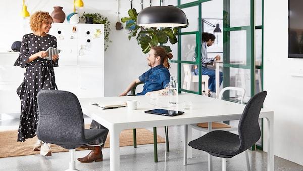 Lelaki duduk di kerusi YPPERLIG bercakap dengan perempuan memegang buku nota di pejabat yang terdapat meja BAKANT dan kerusi pusing pejabat LÅNGFJÄLL.