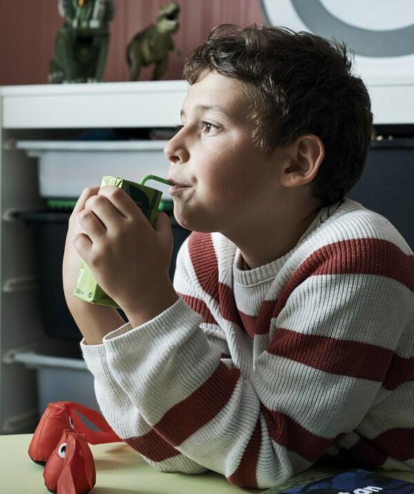 Leo ابن Amélie يشرب من علبة عصير، وحوله الألعاب.