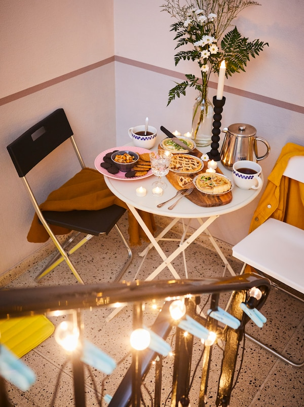 Lépcsőház, GUNDE székekkel és kis asztallal, ételekkel egy FASCINERA vágódeszkán, virágok és kávé.