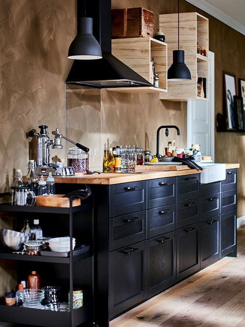 LERHYTTAN black stained kitchen with butcher block countertops and black light fixtures.