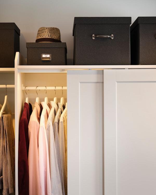 Les chemises sont suspendues dans une armoire blanche, de petites boîtes de rangement brunes sont placées au-dessus de l'armoire.