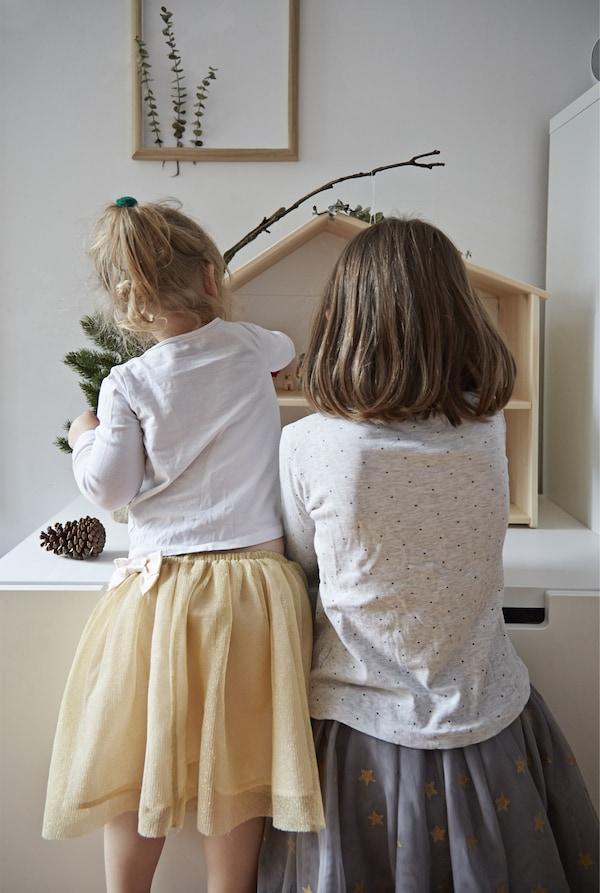 Les enfants jouent avec leur maison de poupées.