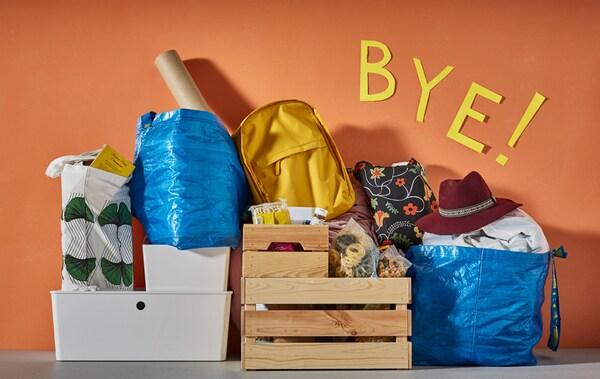 Les essentiels d'un étudiant emballés et déposés contre un mur coloré