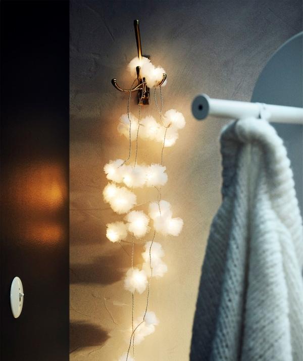 Les flocons lumineux d'une guirlande lumineuse à LED LIVSÅR suspendue au crochet d'une salle de bain.