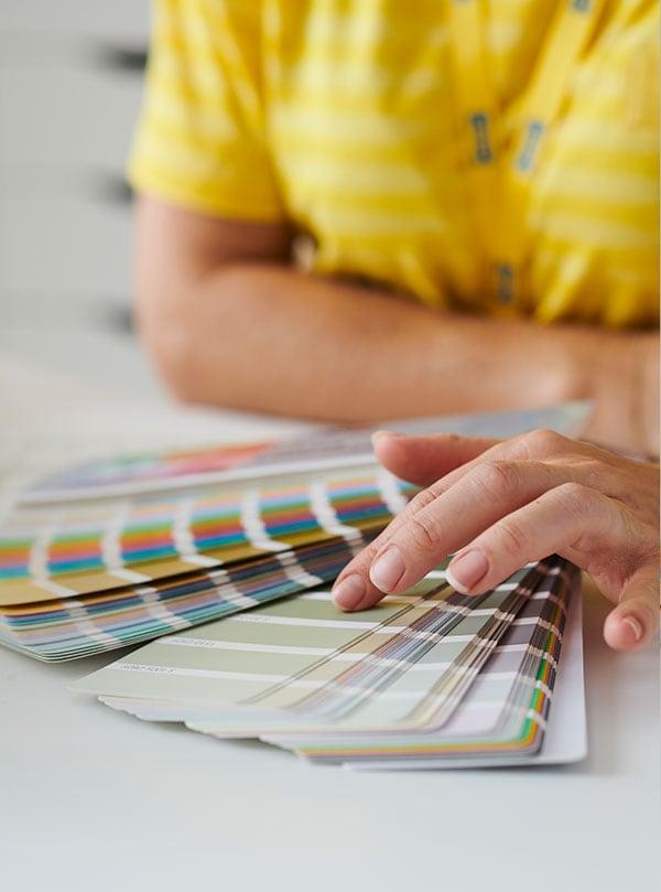 Les mains d'une designer d'intérieur qui tiennent des échantillons de couleurs de peinture.