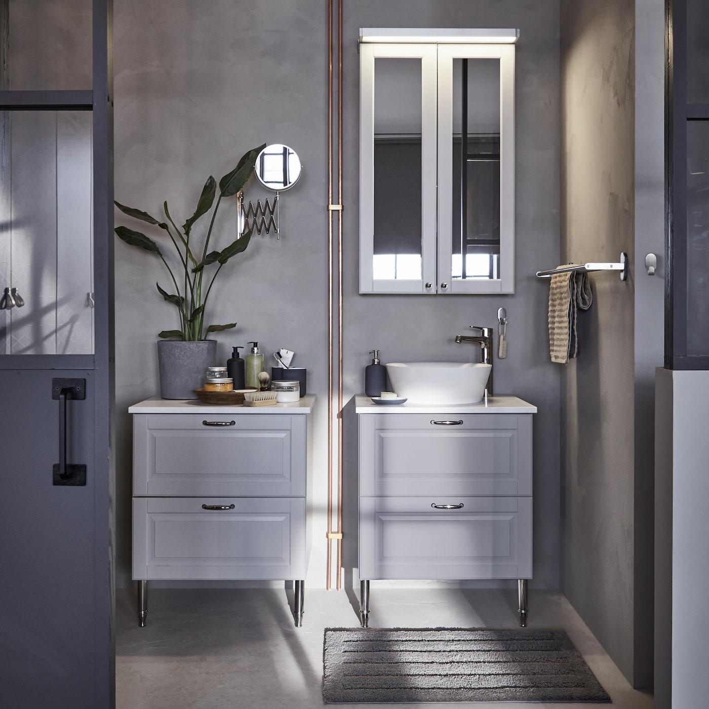 Les meubles lavabo gris clair avec tiroirs IKEA GODMORGON sont réalisés en bois massif et le plan de travail lisse en mélamine masque les traces de doigt et les éclaboussures.