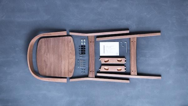 Les pièces et le livret d'instructions d'une chaise en bois STOCKHOLM de IKEA, avant l'assemblage, sont soigneusement disposés sur un plancher gris.