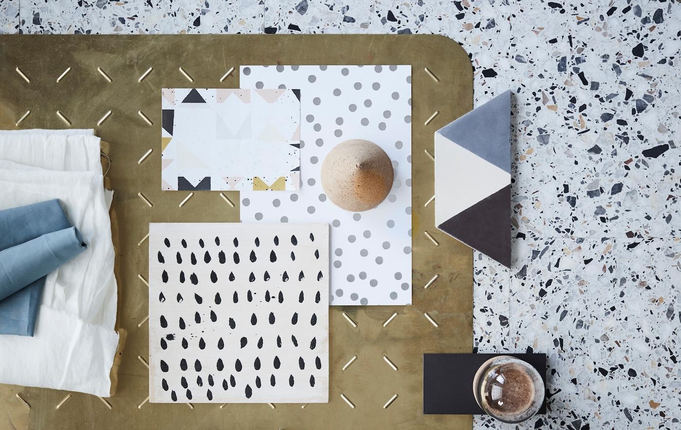 Les tendances déco pour la fin de l'été font la part belle aux textures organiques et aux motifs graphiques. Ici, un mélange de motifs simples comme des pois et des blocs sur du papier et du carrelage, et des notes de textiles, verre et laiton.