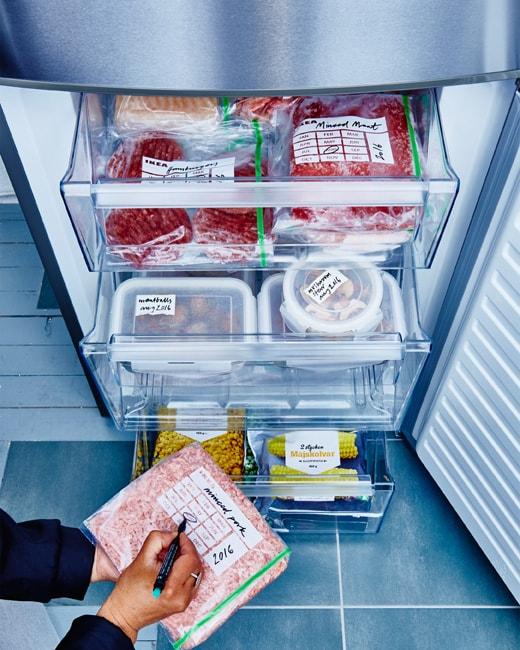 Les tiroirs du congélateur sont ouverts et présentent des aliments bien regroupés, emballés et identifiés.