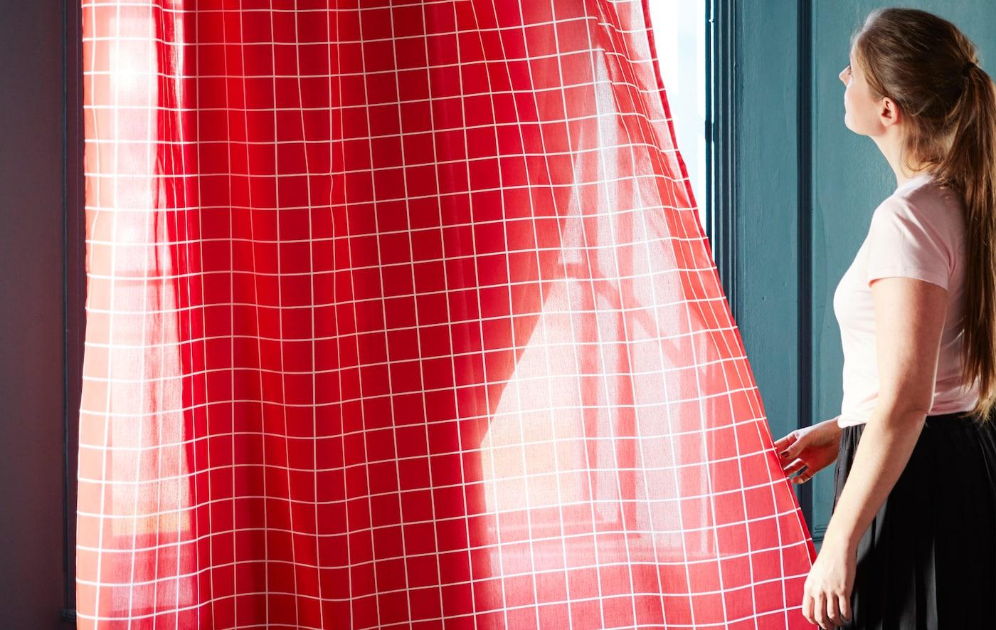 Les voilages IKEA ROSALILL aux lignes blanches sur fond rouge laissant filtrer quelques rayons de soleil.