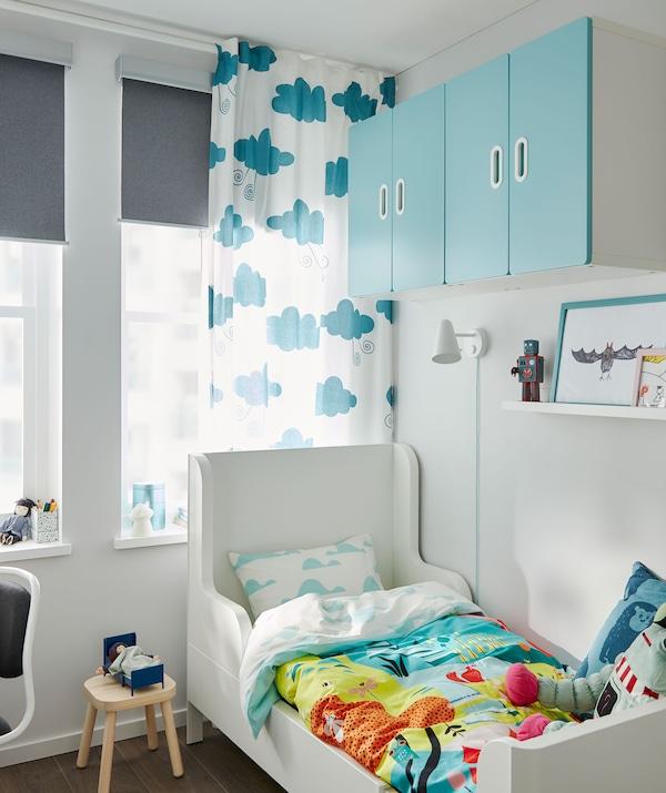 Letto allungabile nell'angolo di una cameretta, copripiumino colorato, pensili alle pareti e una finestra con tende e tende a rullo - IKEA