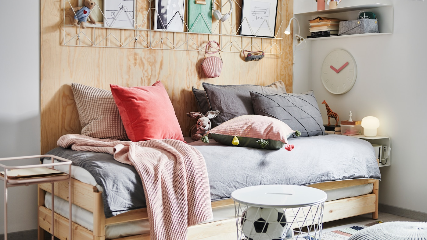 Letto impilabile UTÅKER con tanti cuscini e tessili, comodino, tavolino/contenitore, scaffale da parete e decorazioni.