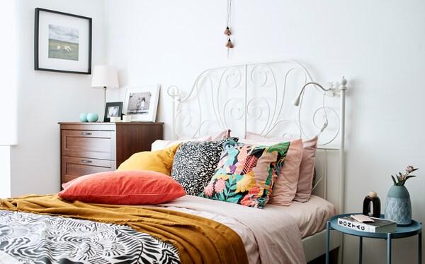 Letto matrimoniale con testiera bianca in ferro battuto, un piumino rosa, un plaid ocra e cuscini rosa, arancioni, gialli, fantasia e monocromo - IKEA