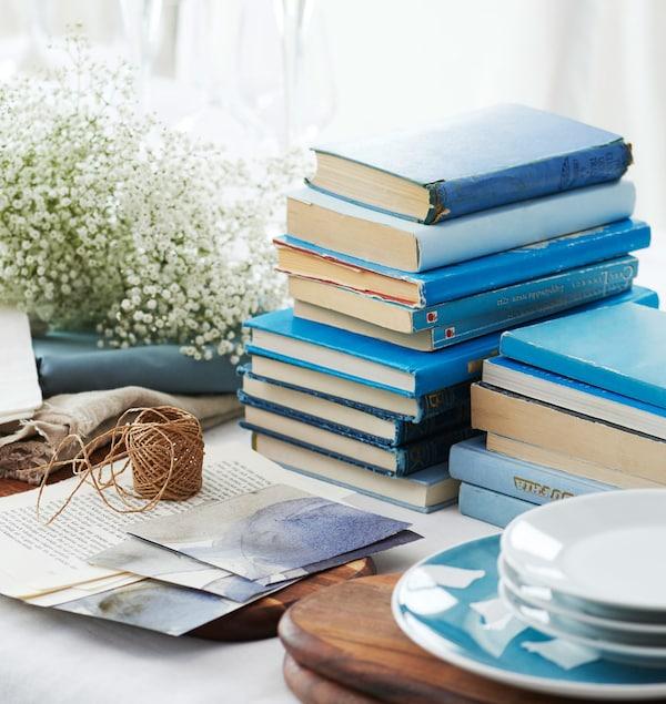 Libros azules, flores velo de novia y platos esperando en el centro de la mesa a ser colocados.