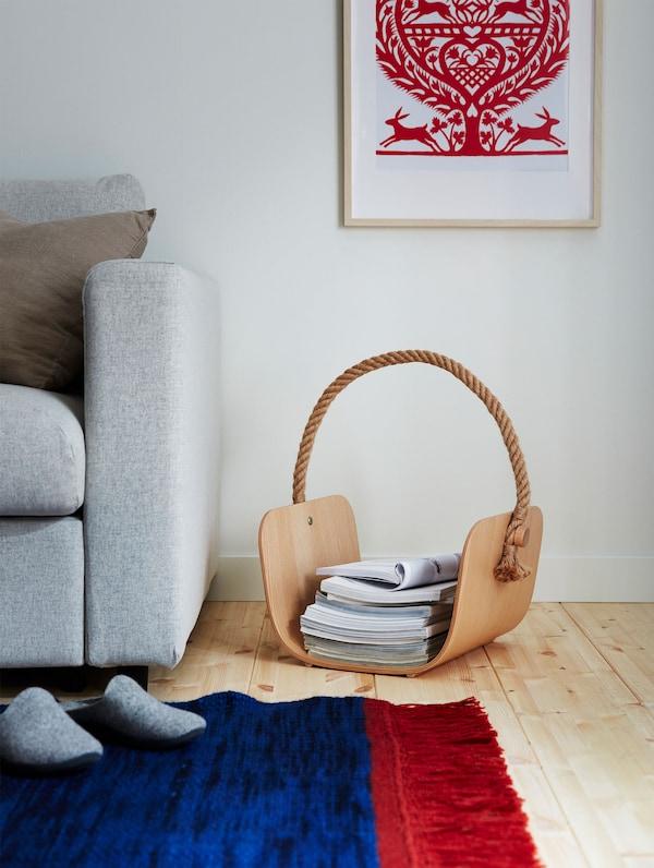 Libros y revistas colocados en el cesto de madera VÄRMER, situado en el suelo junto a una alfombra azul y roja.
