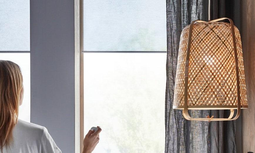 Lichtdurchlässiges Smart Home Rollo wird mit Fernbedienung geöffnet.