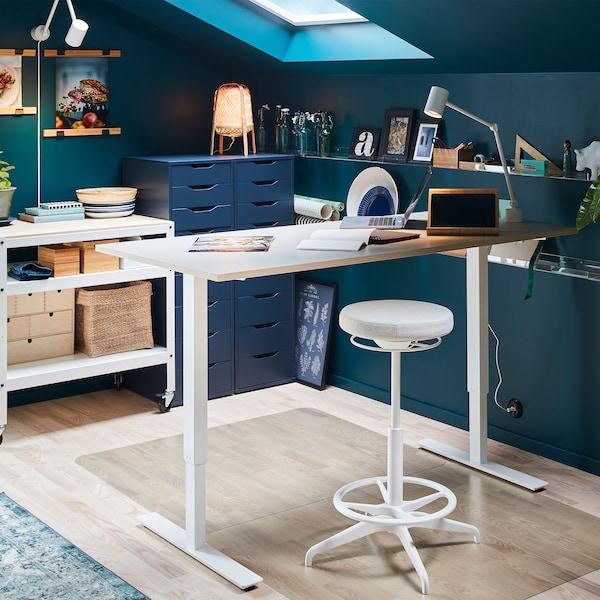 LIDKULLEN sit/stand support stands by a raised sit/stand desk. Transparent floor protectors spare the floor from scratches.