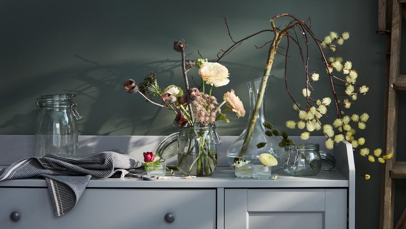 Lien vers «Créez une décoration florale avec ce que vous avez sous la main» - image d'un buffet avec des bocaux et des carafes débordant de fleurs.