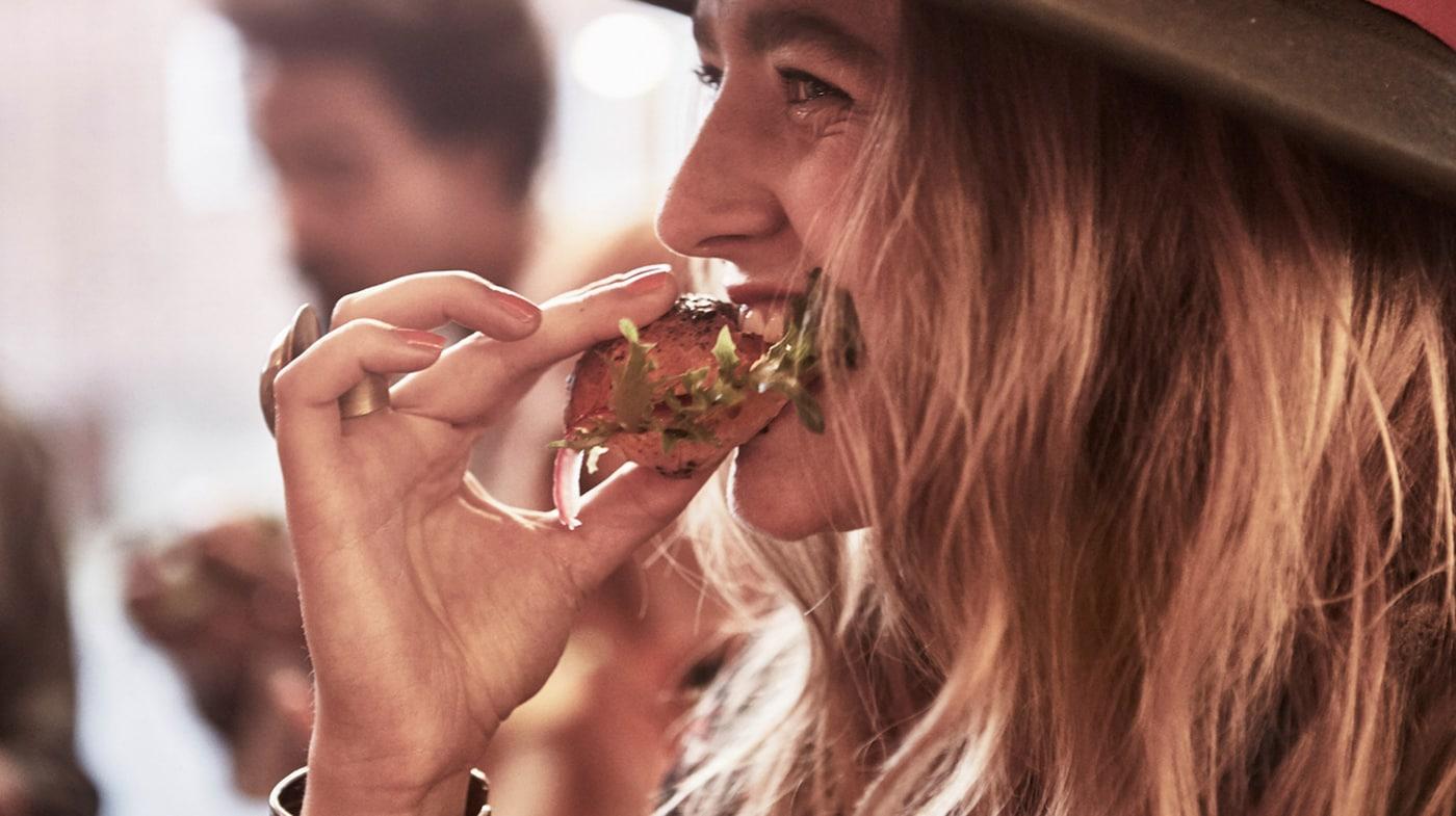 Lien vers Des aliments savoureux et dignes de confiance. Photo d'une jeune femme mordant dans un sandwich au saumon effiloché.