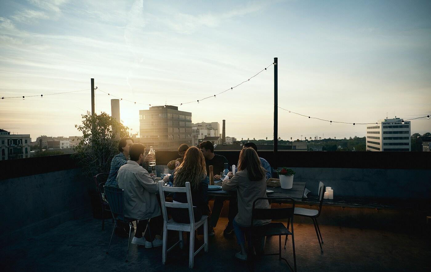 Lien vers IDÉE 'Vers un monde meilleur, une maison à la fois' - photo d'amis réunis autour d'une table sur un toit au coucher de soleil