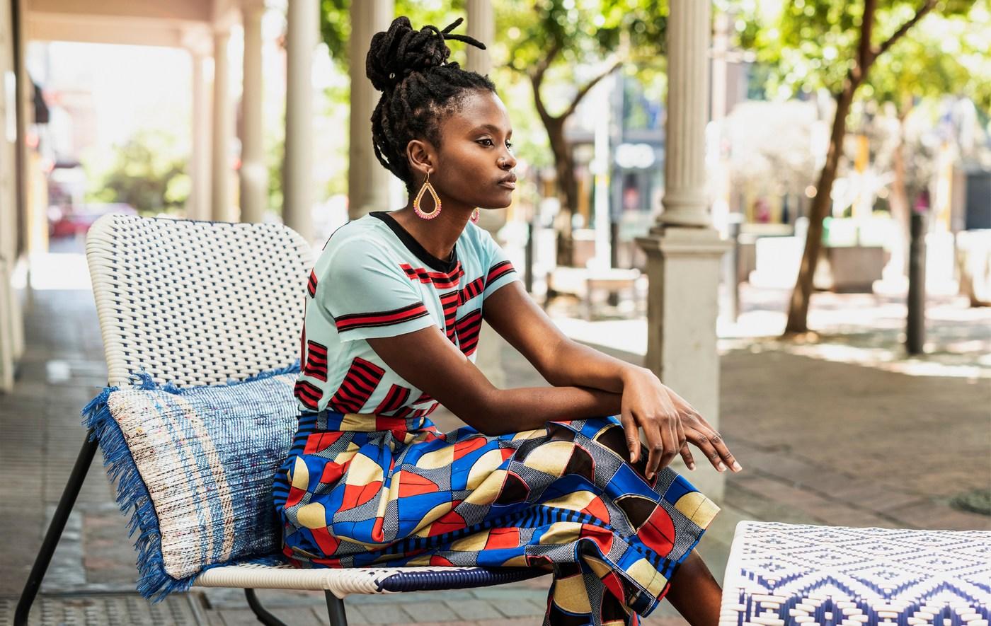Lien vers le Blogue IDÉES «Une nouvelle façon de créer et de concevoir. Photo d'une jeune femme portant des vêtements colorés assise sur une chaise berçante, à l'extérieur.