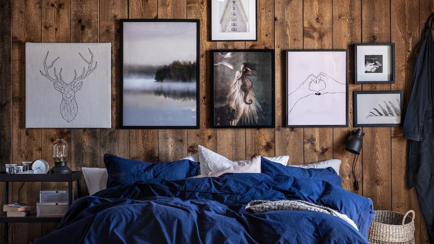 Lien vers «Six conseils pour une décoration murale» - image d'un mur orné de peintures au-dessus d'un lit recouvert de literie bleu roi.