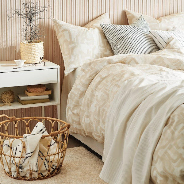 Light bedroom with soft colours and beije and grey quilt and pillows.