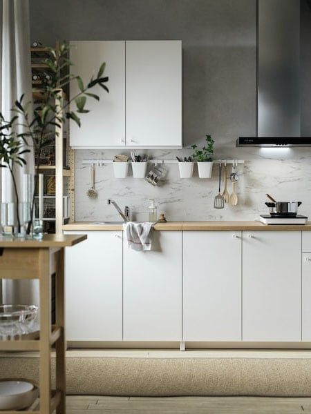 Light bright and modern kitchen with herbs on a rail hung on the back wall