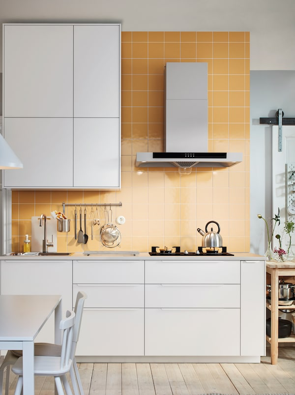 Light-brown tiled kitchen wall. Worktop with sink, hob and utensils, framed above and below by rows of white METOD cabinets.