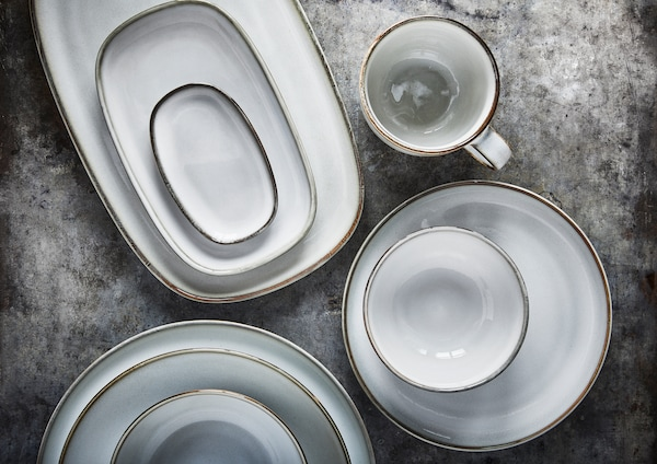 Light grey bowls, plates and serveware in three piles with a cup beside it on a grey surface.