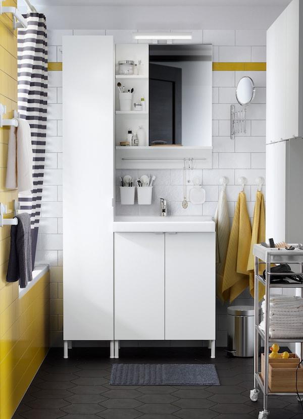 LILLÅNGEN/TALLEVIK-allaskaluste, LILLÅNGEN-seinäkaappi ja LILLÅNGEN-korkea kaappi kylpyhuoneessa, jossa mustaa, valkoista ja keltaista.