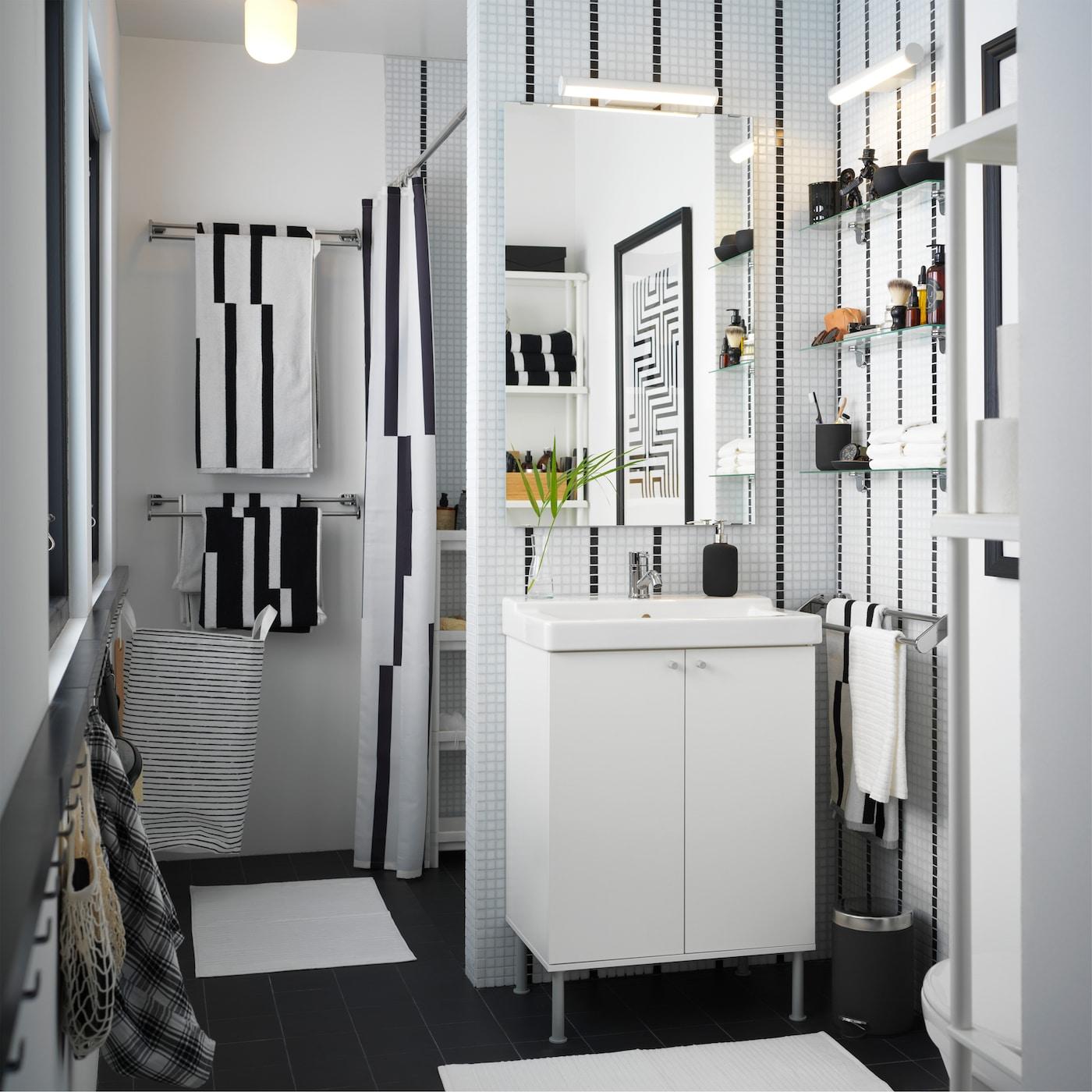 Lille badeværelse i sort og hvidt med hvid vask, stribede håndklæder og et stribet badeforhæng.