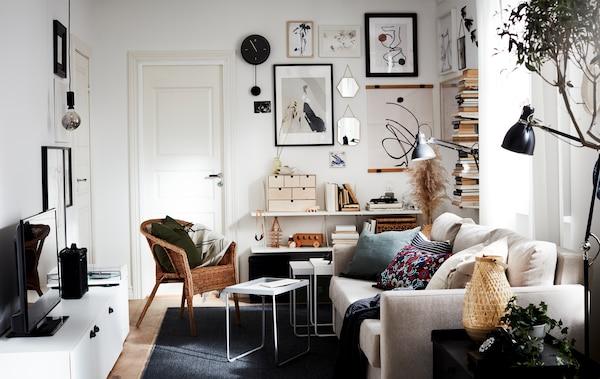 Lille opholdsrum med masser af belysning, en sofa, et tv, en lodret udstilling af bøger og en gallerivæg – alt sammen i neutrale farver.