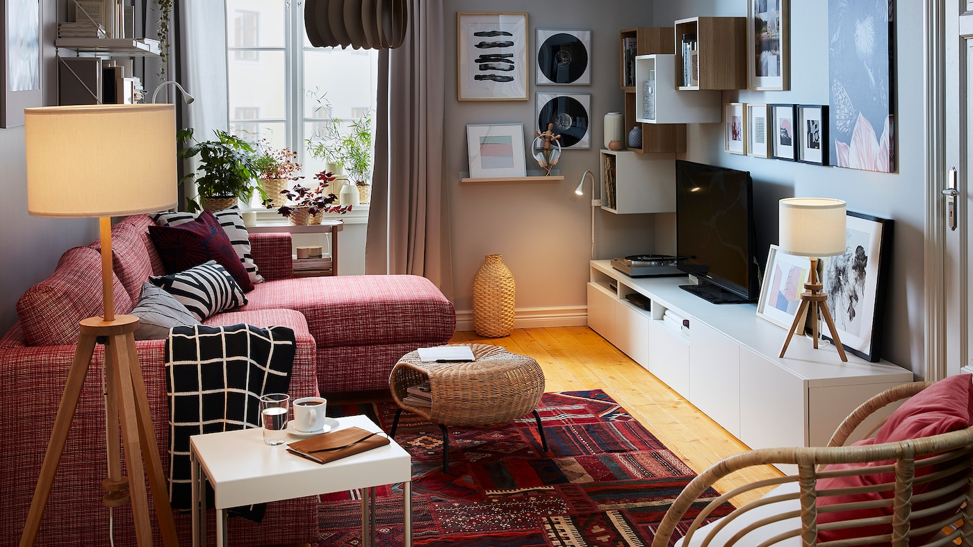 Lille stue med et rødt tæppe med persisk mønster, en rød sofa, grå gardiner, en lænestol af rotting og stemningsbelysning.