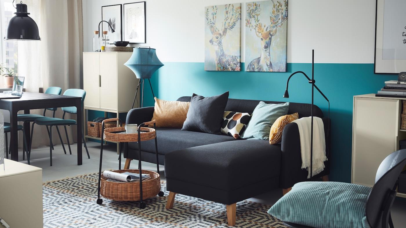 햇살이 비치는 블루와 그레이 톤의 거실에 다크그레이 LINANÄS 리나네스 소파와 긴 의자가 있고 그 앞에 라탄 카트가 있는 모습.