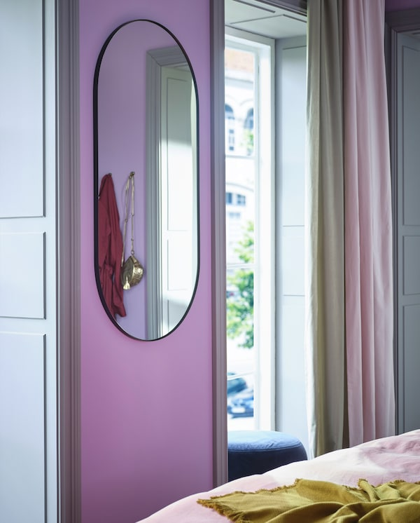 LINDBYN oval mirror with black frame is wall-mounted on a narrow wall between two windows with beige and pink curtains.