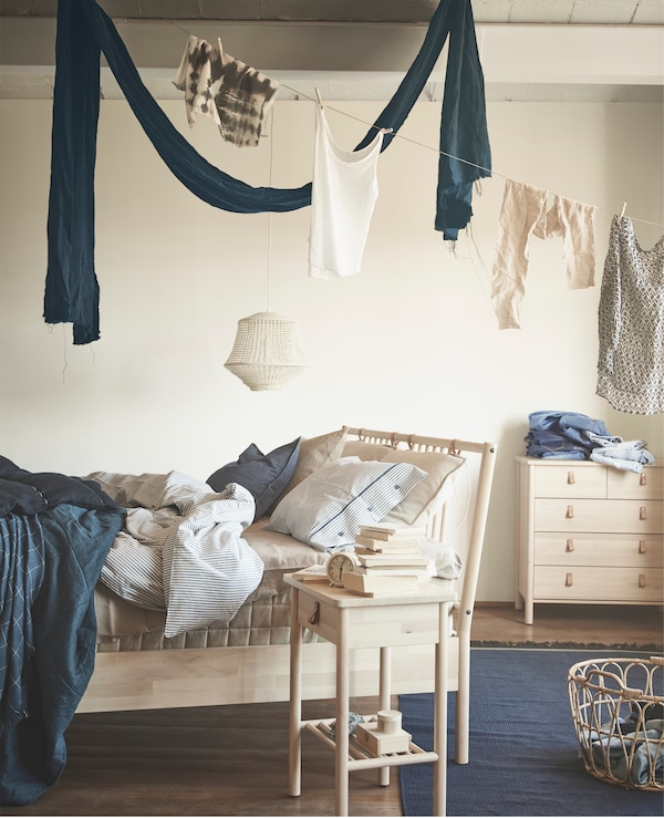 Linen hanging above a wooden bed frame, bedside table and chest of drawers.