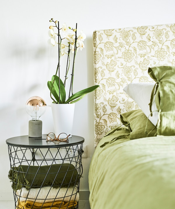 Linen katil berwarna hijau di atas katil dengan kepala katil yang dibuat daripada fabrik paisley berwarna hijau, cermin mata dan pokok orkid terletak di atas meja sisi katil dawai.