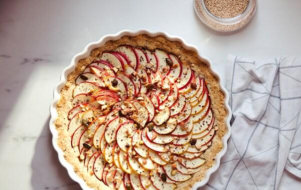 Linge à vaisselle blanc à rayures grises et tarte recouverte de fines tranches de pommes dans un moule à tarte blanc VARDAGEN.