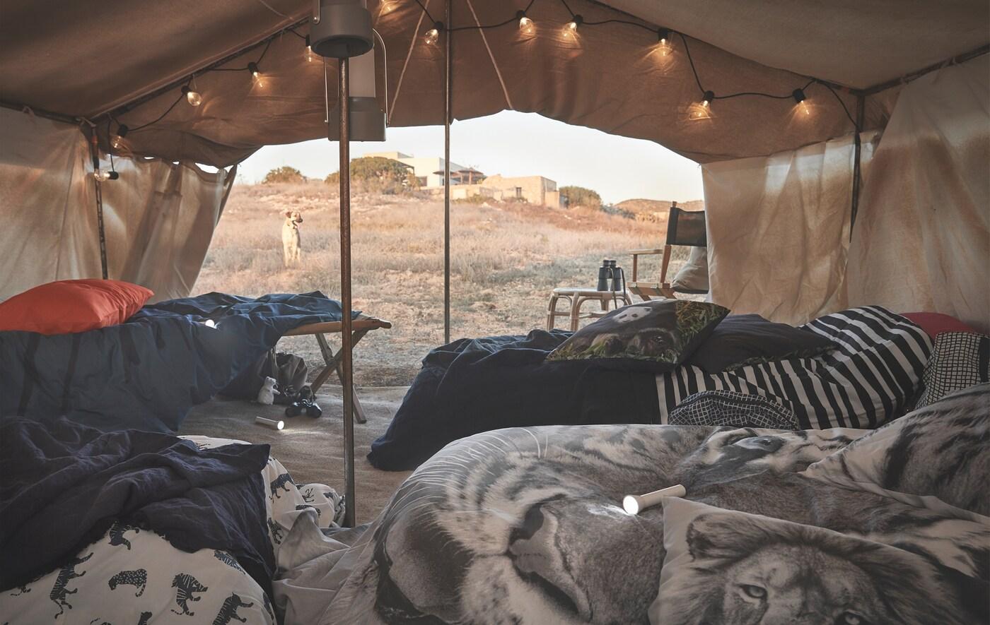 Linge de lit à motifs animaliers habillant des lits sous une tente, dans le désert.